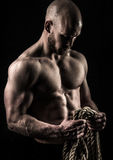 The rope. A very fit yuong male holding a thick rope Royalty Free Stock Photo