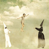 Rope-walker. Woman walking along a tightrope held by two mysterious persons wearing white and black clothes stock image