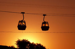 Rope-way at sunset. Silhouette of two trolleys on the rope-way crossing at  sunset Royalty Free Stock Photos