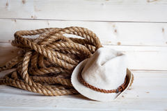 Rope and women`s straw hat in cowboy style on the wooden background Stock Photos