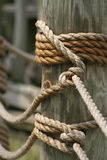 Rope and Wood. Pier pillar with braided rope Stock Photography
