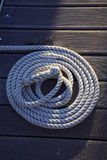 Rope on the wood. A rope on a wood port is half lighting by the evening sun Stock Image