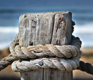 Rope on Wooden Post. Thick rope tied around and knotted on a wooden post, with the blue water of the ocean in the background Royalty Free Stock Photo