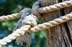 Rope on wooden post. Part of old wooden fence with a rope Stock Photo