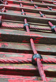 Red ladder. Wet ladder with guiding rope painted in red and wooden steps Stock Images