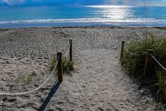 Path to the Silver Sea. A roped path to a Florida beach with the sun shining on the smooth silver water Stock Image