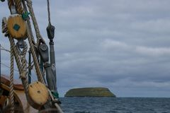 Ropes of an ancient whaler in the foreground and in the background the island where the puffins live.  stock image