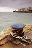 Ropes around maritime bollard. Rope and chain around maritime bollard on quayside with sea and Swanage town coastline in background Royalty Free Stock Photo