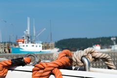 Ropes on boat in marina. Orange and natural ropes tied to anchoring pins on boat in a harbor with other marina vessels in distance. Blurred background. Copy royalty free stock image