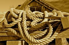 Ropes of the Boating industry. Old ropes lie on a dock with an old fishing and boating shack in the background Royalty Free Stock Photography