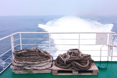 Ropes on the deck of a ferry. Ropes coiled up on pallets on the desk of a moving ferry Royalty Free Stock Photos