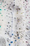 Ropes Footholds and Bells on Rock Climbing Wall Stock Photography