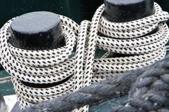 2 ship bollards with lashed ropes. Ropes made of synthetic fibers spotted in black and White, Ship bollard wrapped in braided rope, iron bollard, boat is secured royalty free stock image