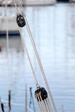 Ropes and pulleys, detail. A detailed view of two pulleys of a sailboat, with ropes, at the marina, blurred background,  portrait cut Stock Photo