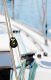 Ropes and pulleys, detail. A detailed view of two pulleys of a sailboat, with ropes, at the marina, blurred background,  portrait cut Stock Photos