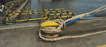 Ropes securing marine vessel in Singapore shipyard. Singapore shipyard capstan tying down ropes for cargo ship Stock Images