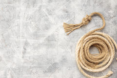 Ropes tied with knots on a gray background. Ship rope knot on light gray concrete background. Top view. Place for text stock images