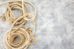 Ropes tied with knots on a gray background. White rope with knot on gray background. Top view. Place for text stock photography