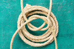 Ropes tied with knots on turquoise background. Ship rope knot on turquoise background. Top view royalty free stock photo