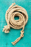 Ropes tied with knots on turquoise background. Ship rope knot on turquoise background. Top view stock photos