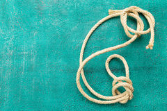 Ropes tied with knots on turquoise background. Ship rope knot on turquoise background. Top view. Place for text stock image