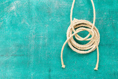 Ropes tied with knots on turquoise background. Ship rope knot on turquoise background. Top view. Place for text royalty free stock image