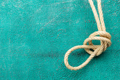 Ropes tied with knots on turquoise background. Ship rope knot on turquoise background. Top view. Place for text stock photo