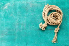 Ropes tied with knots on turquoise background. Ship rope knot on turquoise background. Top view. Place for text stock photography