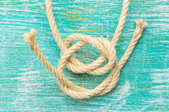 Ropes tied with knots on turquoise background. Ship rope knot on turquoise wooden background. Top view royalty free stock photography