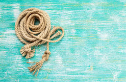 Ropes tied with knots on turquoise background. Ship rope knot on turquoise wooden background. Top view. Place for text stock photography