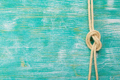 Ropes tied with knots on turquoise background. Ship rope knot on turquoise wooden background. Top view. Place for text stock photos
