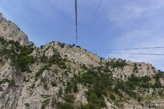 Ropes tourist suspension lift climb to the top of the high Crimean mountain AI-Petri. The rocks are beautifully overgrown with. Pine trees. Clear summer day royalty free stock image