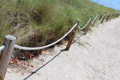 Ropes and wood posts leading onto a sandy beach at ocean Stock Photo