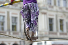 Rope walk. Girls balancing act with the help of a pole and metal wheel Stock Photo