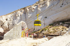 Ropeway above the grotto, yellow cab goes down Royalty Free Stock Photography