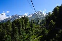 Ropeway cabines in de bergen van de Kaukasus met bos en sneeuw worden behandeld die stock foto