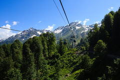 Ropeway cabins in caucasus mountains covered with forest and snow Stock Photo