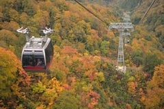 Ropeway lift through vibrant Autumn foliage Royalty Free Stock Photo