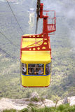 Ropeway on a mountain Ai-Petri. CRIMEA, YALTA - May 04.2010: Yellow carriage of passenger ropeway from a city Yalta on the top of mountain Ai-Petri Stock Photo