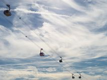 Ropeway with wagons on a background of blue sky with clouds. Stock Image