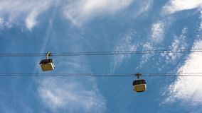 Ropeway with wagons on a background of blue sky with clouds. Ropeway with wagons on a background of blue sky with clouds Stock Photography