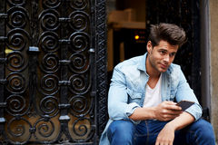 Сropped shot of a fashionable man using his mobile phone in urban setting Stock Images