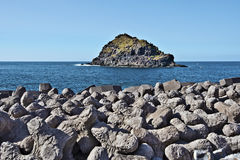 Roque-de-Garachico islet in north of Tenerife island. Seen from Garachico village. Concrete Tetrapods of breakwaters coastline pretention are at foreground stock photos