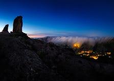 Roque Nublo峰顶和阿特纳拉村庄看法在夜之前 库存照片