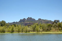 Roquebrune from lake. Le Rocher de Roquebrune near Frejus, France from a small lake beside river Argens stock images