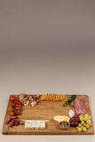 Roquefort cheese, biscuits and ham with various ingredients on chopping board. Against white background Stock Photography