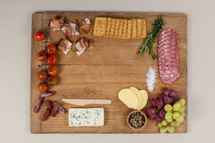 Roquefort cheese, biscuits and ham with various ingredients on chopping board Royalty Free Stock Photo