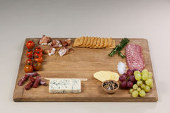 Roquefort cheese, biscuits and ham with various ingredients on chopping board. Against white background Stock Photos