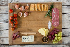 Roquefort cheese, biscuits and ham with various ingredients on chopping board. Against white background Stock Image