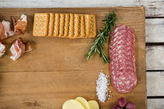 Roquefort cheese, biscuits and ham with various ingredients on chopping board. Against white background Royalty Free Stock Images